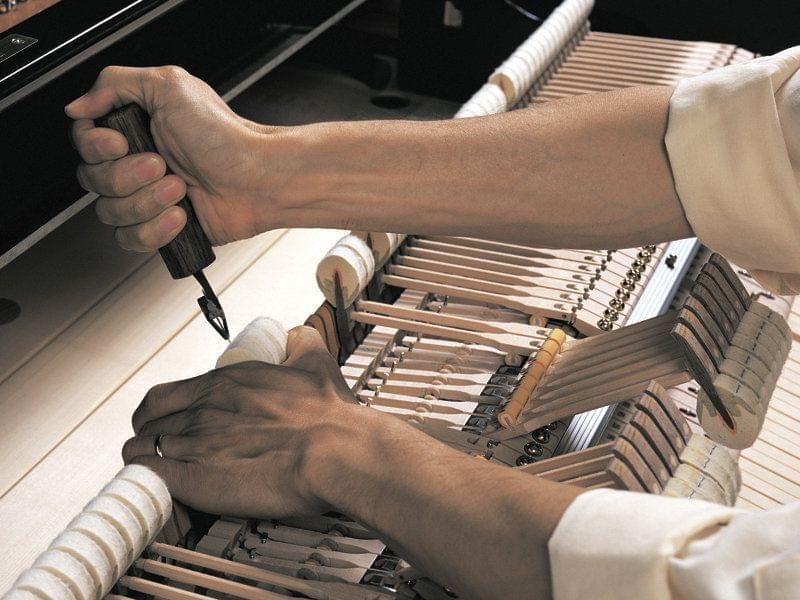 Imagen de un técnico trabajando en el interior de un piano