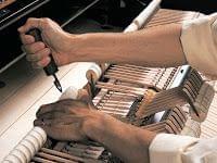 Imagen de un técnico trabajando en un piano. Vista de los martillos del interior